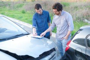 due uomini che compilano cid dopo incidente